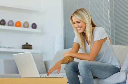 Smiling young woman using her laptop