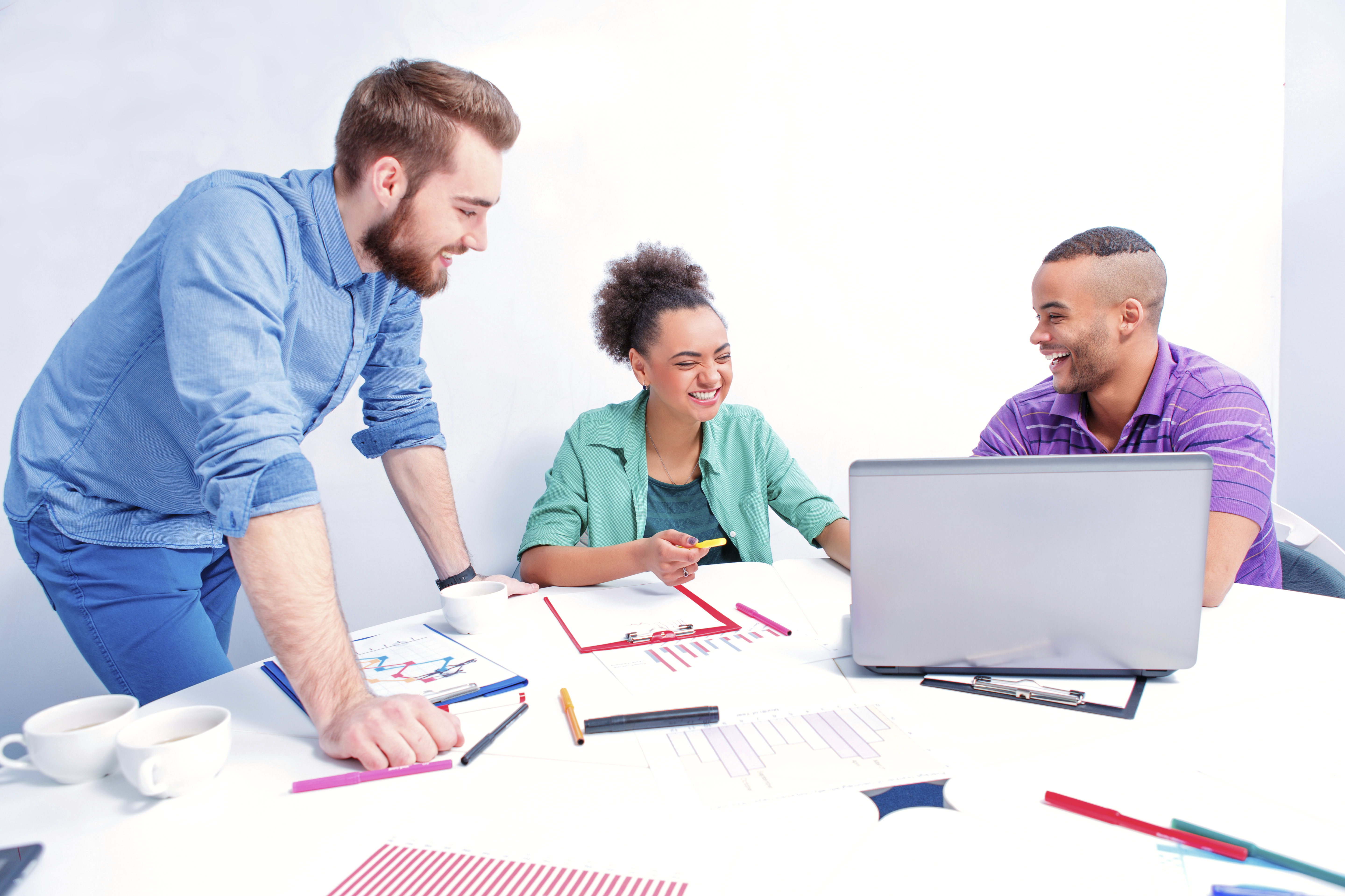 Creative professionals. Group of cheerful business people in smart casual wear discussing something while having a brain storming in the meeting room